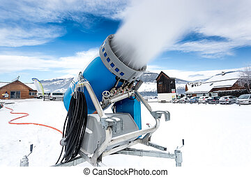snow cannon making artificial snow at cold on ski slope -...