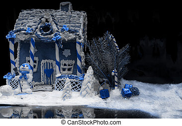 Big snow-covered homemade gingerbread house, a sprig of Christmas tree and a sugar mastic snowman in white and blue tones on dark background