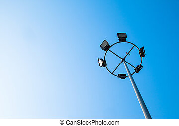 Big spotlight pole on blue sky background