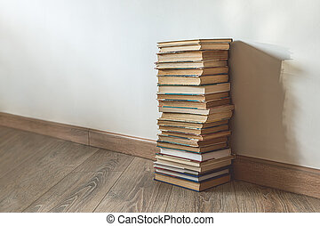 Big stack of old books over white wall