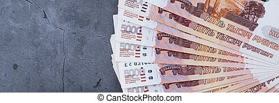 Big stack of Russian money banknotes of five thousand rubles lying fan on a grey cement background.