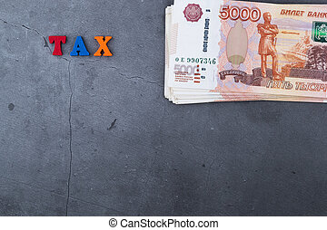 Big stack of Russian money banknotes of five thousand rubles lying on a grey cement background.