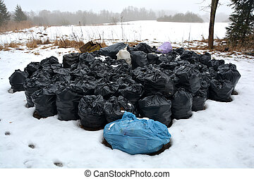 stack rubbish trash full plastic sacks on snow in park