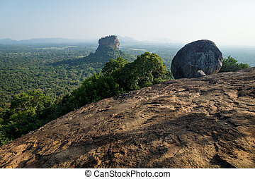 Big Stone on Pidurangala Rock with view on Lions Rock surrounded by forest in Sigiriya, Sri Lanka
