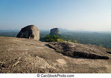 Big Stone on Pidurangala Rock with view on Lions Rock with mountain background in Sigiriya, Sri Lanka