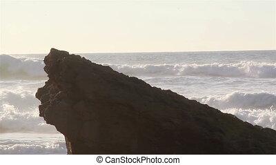 Big stone on the beach splashing on big rocks - Big stone on...