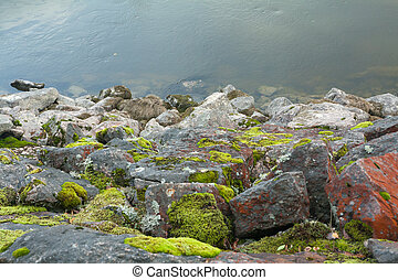 Big stones are on the lake shore in Finland at summer.