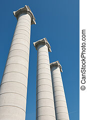 Big, strong stone columns on the street in Barcelona in Spain from bottom view, hill Montjuic.