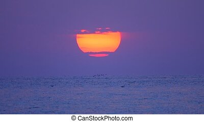 big sun rises over the sea early in the morning