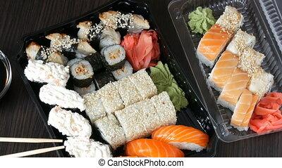 Big sushi set with variety of sushi rolls, maki, nigiri, gunkan on a stylish dark background. Soy sauce and bamboo chopsticks lie nearby