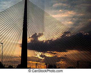 Big suspension bridge tower at sunset - sunrays bursting through the clouds