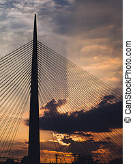 Big suspension bridge tower at sunset - sunrays through the clouds in the background