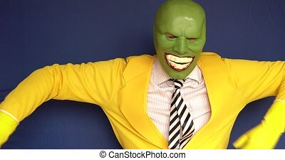 Big takes off the mask rejoices with a kind look on a blue background with studio light bright blue eyes clothes yellow