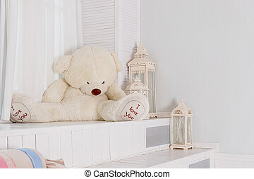 Big teddy bear near big white lantern, pillows in girly room. playroom interior. Beautiful child's room in pastel tones and toys. Copy space. big white bear. Interior room for a child. Cozy atmosphere inside the house.
