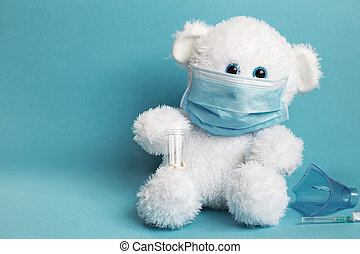 big teddy toy bear are sitting in white medical mask with mask for inhalation, syringe and tablets on a blue background.
