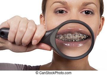 funny looking young dark hair caucasian girl with magnifying glass near mouth smiling isolated over white background