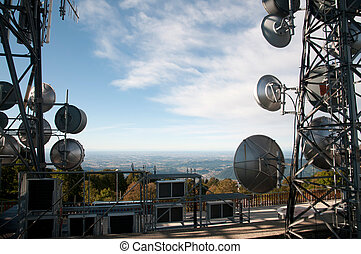 Big television and radio tower with several parabolic antenna on high quote (mountain) - Roncola (Italy)