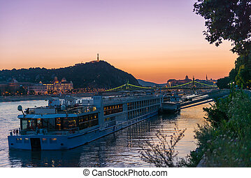 big touristic steamboat on Danube at sunset with cityscape...