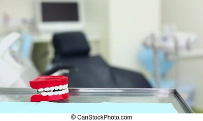 Big toy jaw clicks his teeth on table in dental surgery