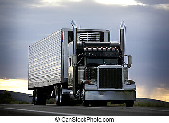 truck - big truck driving on a highway with cloudy sky in...