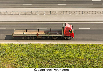 Big truck with a long open trailer on the highway.