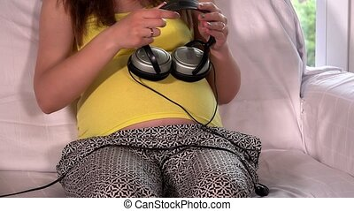 Big tummy with baby inside with headphones on playing music....