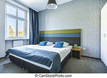 Big twin bed in blue hotel apartment - Big twin bed in...