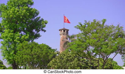 Big Vietnamese flag waving on the top of a tower on the territory of the Museum of War in Hanoi. Vietnam's war for independence. Travel to Vietnam concept.