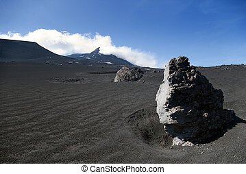 Big volcanic rock with Etna mountain in background, Sicily,...