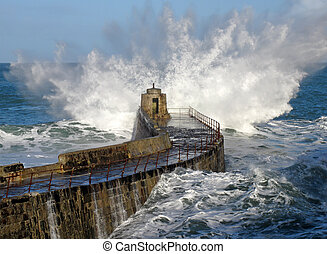 Big wave splash on Portreath pier, Cornwall UK.