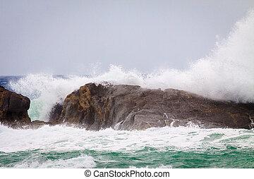 Big waves crashing against of the rocks.