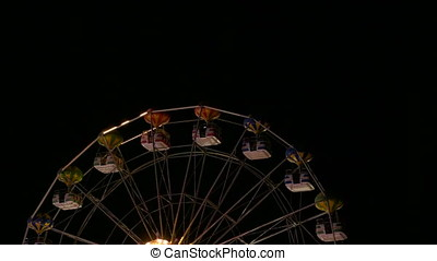 Big wheel carousel attraction slowly rotating in the night