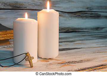 Big white burning candles and cross.