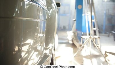 Big white car standing indoor - in car service station at...
