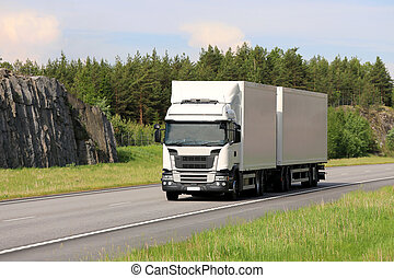 Big white cargo truck transports goods along motorway on a beautiful day of summer.