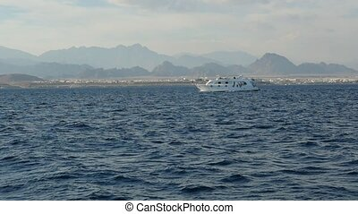 Big white motorboat floating in the Red Sea with hilly coast...