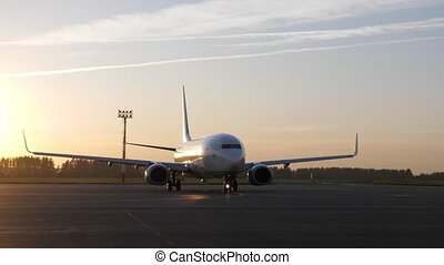 Passenger jet on airstrip in airport airfield. Big white plane preparing to fly starting to move on runway at sunset, front view. Spotting hobby concept.