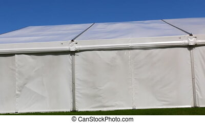 Wind moves backside of big marquee built on green grass on a sunny day with clear blue sky