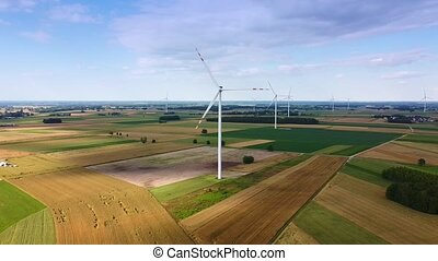 Aerial long shot of big windmills from drone in summer. Wonderful bird eye of wind energy mill.