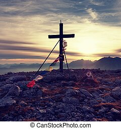 Big wooden cross at mountain peak in wind with Buddhist praying flags. Cross on top of Alp peak