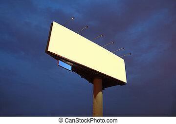 Big yellow billboard at night, bright illumination, dark blue sky