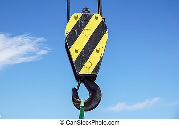 Big yellow construction crane on blue sky background