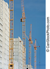 Big yellow cranes constructing a new high rise.
