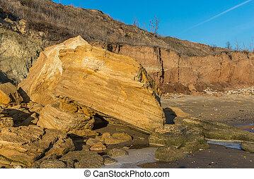 Big yellow stones on the shore