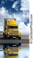 Big yellow trailer on the road over dramatic blue sky with ...