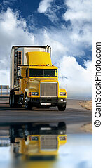 Big yellow trailer on the road over dramatic blue sky with...