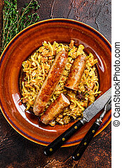 Bigos Stewed cabbage with mushrooms and meat sausages on a plate. Dark background. Top view