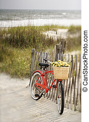 Bike at beach. - Red vintage bicycle with basket and flowers...