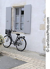 Old fashioned style bicycle leaning against a window.