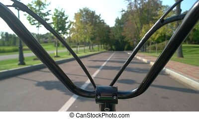 Bike handlebars on road background. Electric scooter moving...